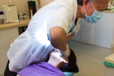 Zahnarzt-behandelt-Patientin-in-Zahnarztpraxis