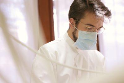 Zahnarzt-bei-der-Arbeit-im-weissen-kittel